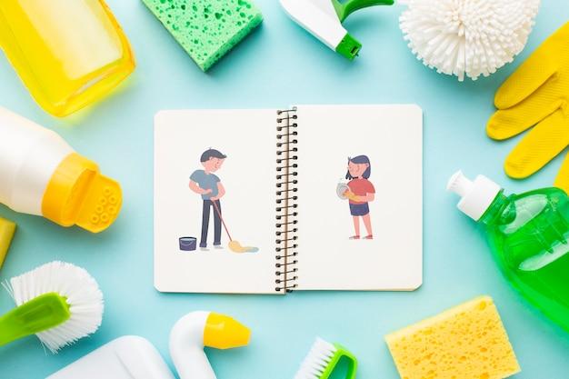 Notebookmodel omringd door schoonmaakgereedschap Gratis Psd
