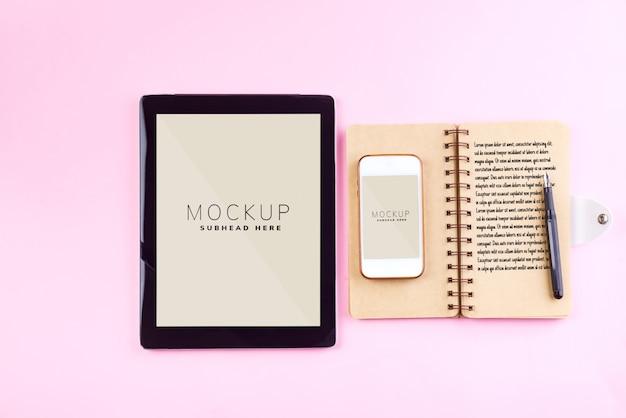 Notebooks, tablet, pen en smartphone op een pastel roze tafel Premium Psd