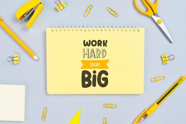 Notitieboekje met positieve bericht en office-hulpmiddelen naast Gratis Psd