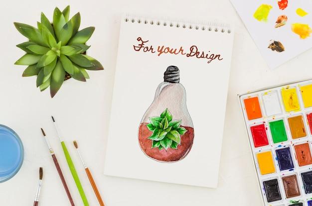 Notitieboekje met realistische tekening en acrylpallet ernaast Gratis Psd
