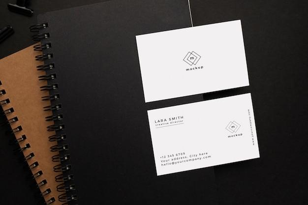 Notitieboekjes en visitekaartje mockup met zwart element op zwarte achtergrond Gratis Psd