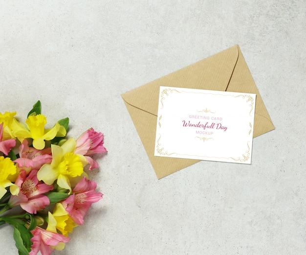 Onechte uitnodigingskaart op grijze achtergrond met bloemen en envelop Premium Psd