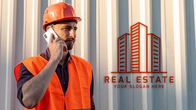 Onroerende goederenmens met bouwvakker die op telefoon spreken Gratis Psd