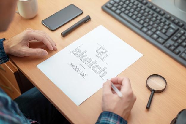Ontwerper schetsmodel. papier op het bureau. uitzicht over schouder. computertoetsenbord, telefoon, pen, koffiemok, vergrootglas naast Premium Psd