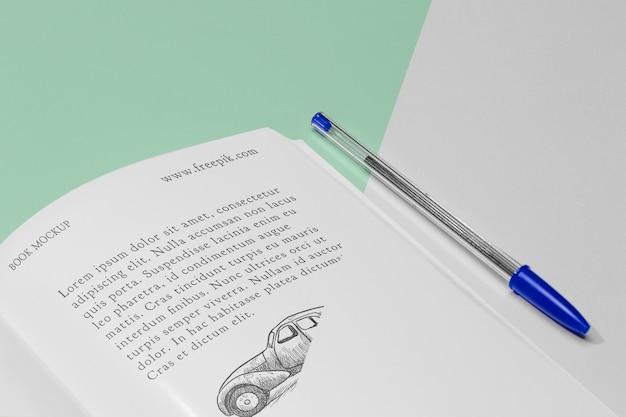 Open boekmodel met hoge hoek met pen Gratis Psd