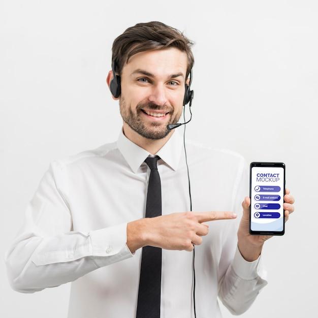Operador de centro de llamadas que muestra un teléfono móvil de maqueta PSD gratuito