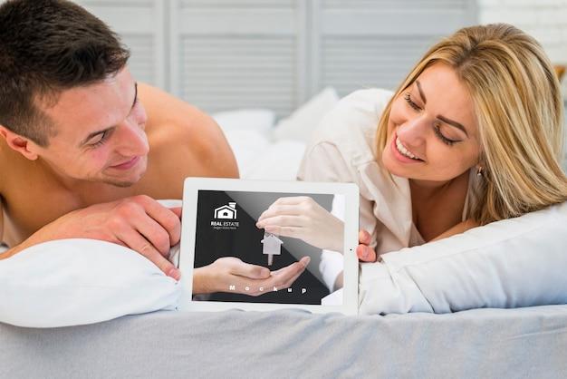 Paar in bed met tabletmodel voor valentijnskaart Gratis Psd
