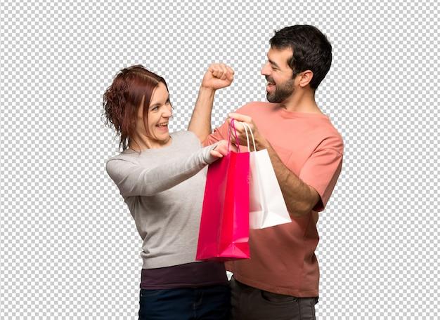 Paar in valentijn dag houden boodschappentassen in overwinning positie Premium Psd