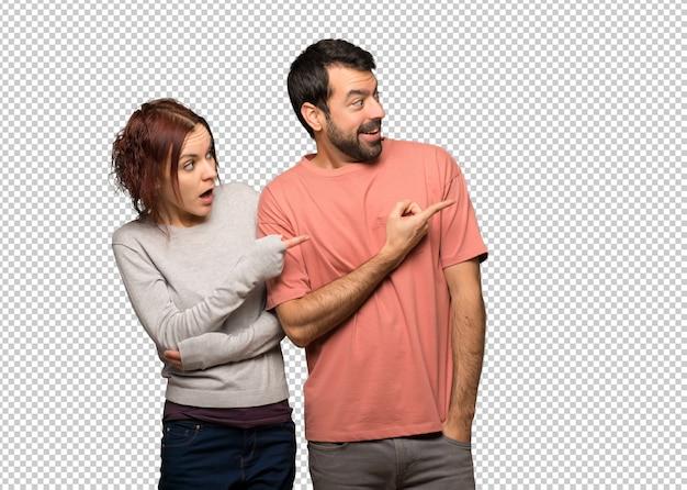 Paar in valentijnskaartdag wijzende vinger aan de kant met een verrast gezicht Premium Psd