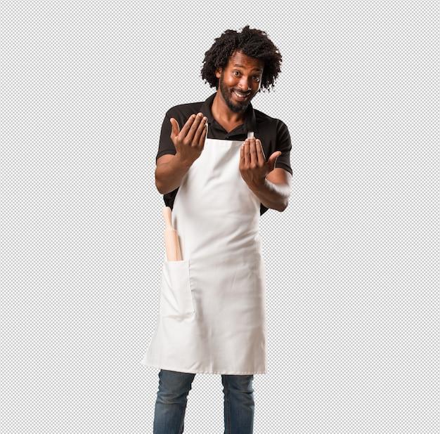 Panettiere afroamericano bello che invita a venire, sicuro e sorridente facendo un gesto con la mano, essendo positivo e amichevole Psd Premium