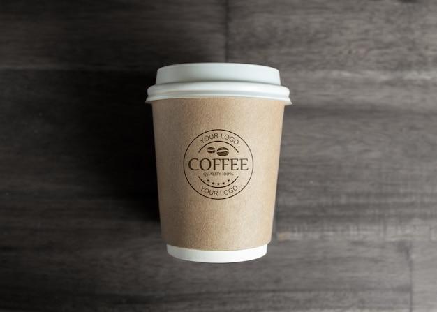 Papieren koffiekopje mockup op houten tafel Gratis Psd