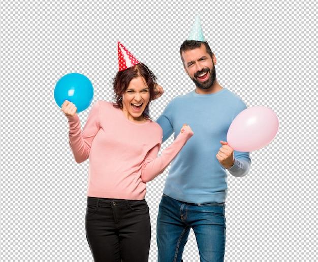 Pareja con globos y sombreros de cumpleaños celebrando una victoria y feliz por haber ganado un premio PSD Premium