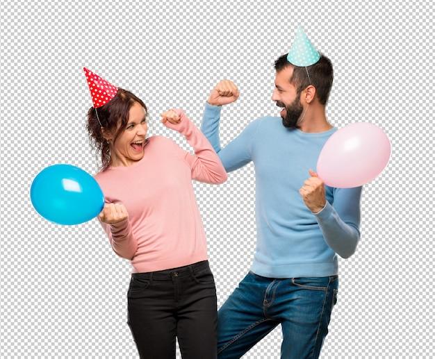 Pareja con globos y sombreros de cumpleaños celebrando una victoria en  posición de ganador  88192011cda