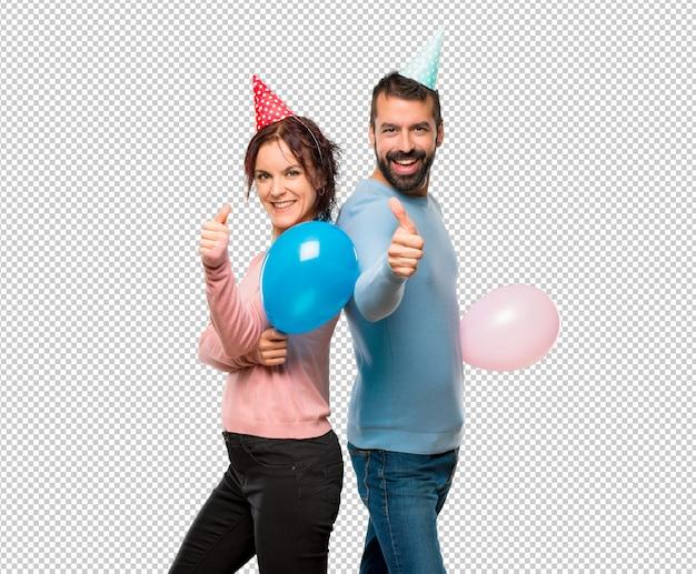 Pareja con globos y sombreros de cumpleaños dando un pulgar arriba gesto y  sonriendo  5fc545fe5e8