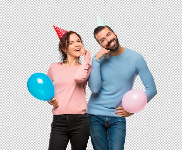 Pareja con globos y sombreros de cumpleaños haciendo gesto de ... bea80480b89