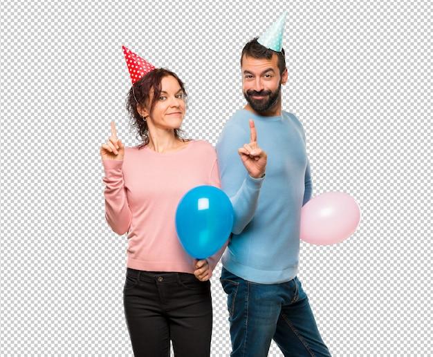 Pareja con globos y sombreros de cumpleaños mostrando y levantando un dedo  en señal de la mejor  1560876eb4a