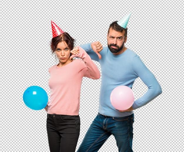 Pareja con globos y sombreros de cumpleaños mostrando el pulgar hacia abajo  signo con expresión negativa  c4eb1a777ab
