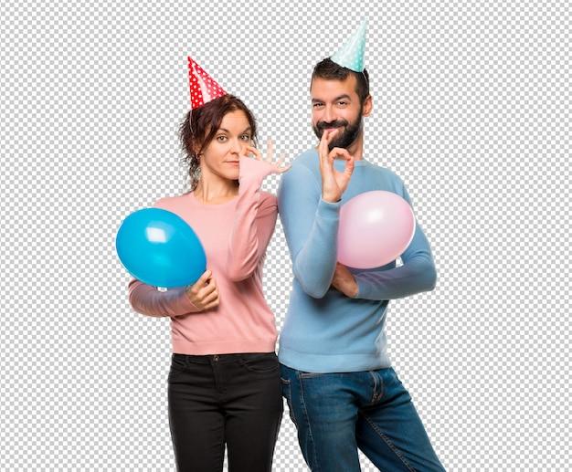 Pareja con globos y sombreros de cumpleaños que muestra un signo de ... acceab43fdb