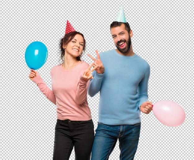 Pareja con globos y sombreros de cumpleaños sonriendo y mostrando el ... 19711d795d0