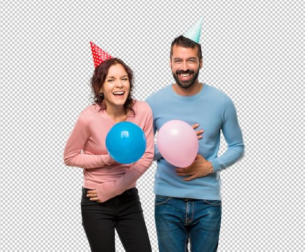 Pareja con globos y sombreros de cumpleaños sonriendo mucho mientras se  pone las manos en el pecho  3606b7a2653