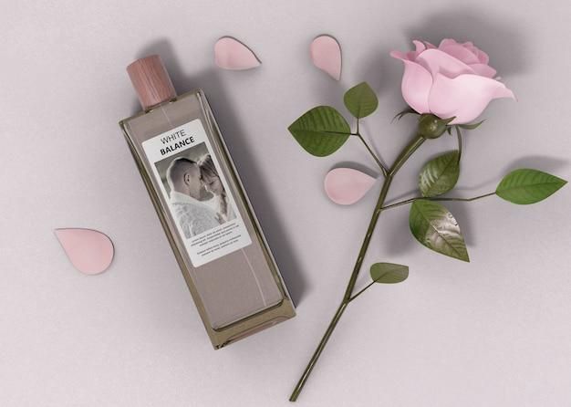 Parfumfles naast roos op tafel Gratis Psd