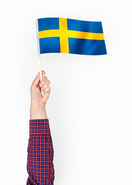 Persona che sventola la bandiera del regno di svezia Psd Premium
