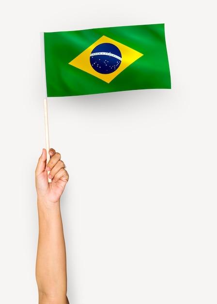 Persona che sventola la bandiera della repubblica federativa del brasile Psd Premium