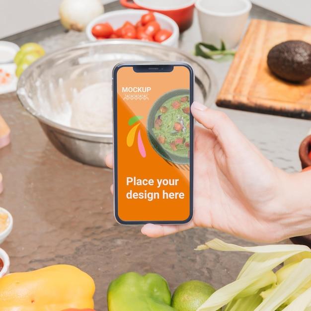 Persona sosteniendo una maqueta de comida saludable de teléfono móvil PSD gratuito