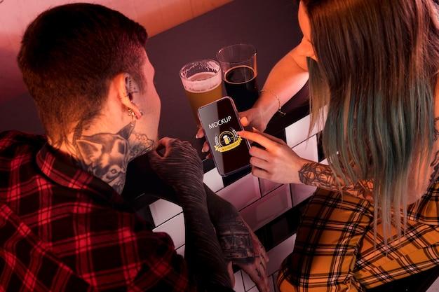 Personas de alto ángulo con maqueta de cerveza y teléfono PSD gratuito