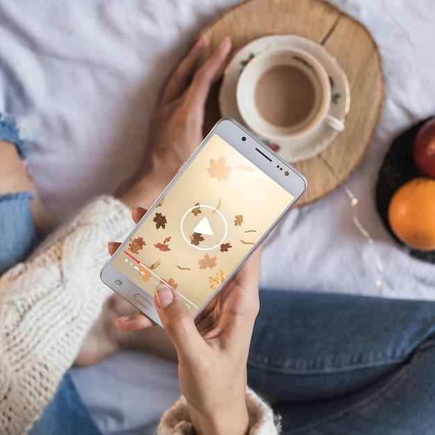 Persoon op bed die smartphone met de herfstconcept bekijken Gratis Psd