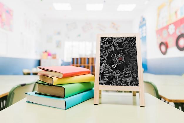 Piccolo mock-up di lavagna accanto a libri colorati Psd Gratuite