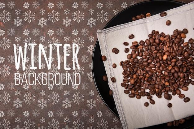 Plaat met koffiebonen en de winterachtergrond Gratis Psd
