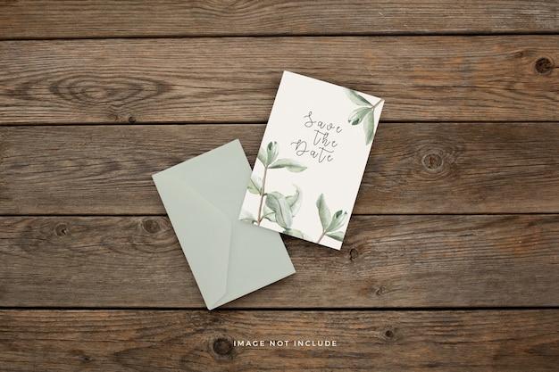 Plantilla de invitación de boda con hermosas hojas sobre un fondo de madera marrón PSD gratuito