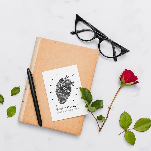 Plat boek met bril en roos Gratis Psd