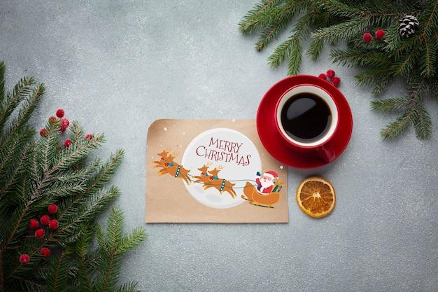 Plat kopje koffie met met vrolijke kerst brief en pijnboombladeren Gratis Psd