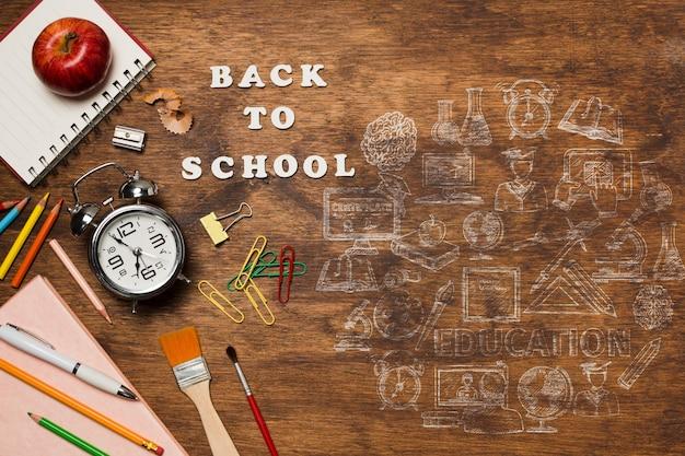Plat lag frame met schoolelementen op houten achtergrond Gratis Psd