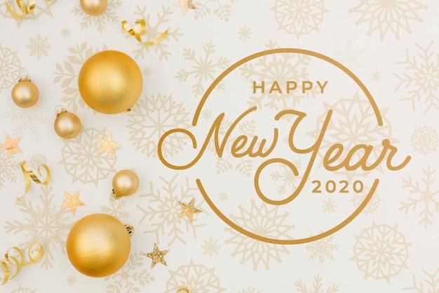 Plat lag gelukkig nieuwjaar 2020 mock-up met gouden kerstballen Gratis Psd