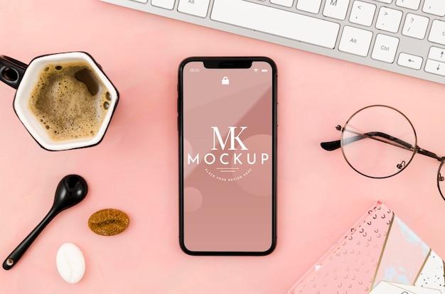 Plat lag smartphone mock-up met koffie en glazen Gratis Psd