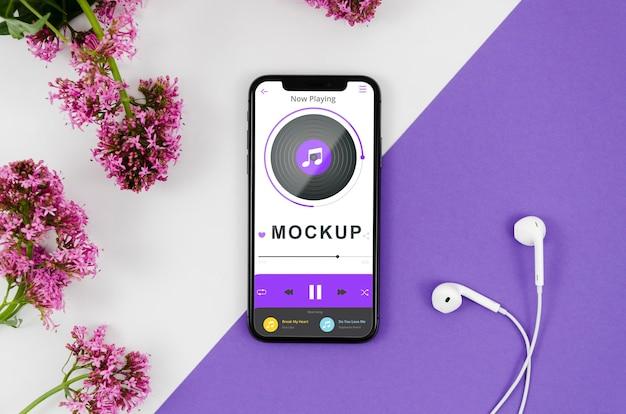 Plat lag smartphone mock-up met oortelefoons en bloemen Gratis Psd
