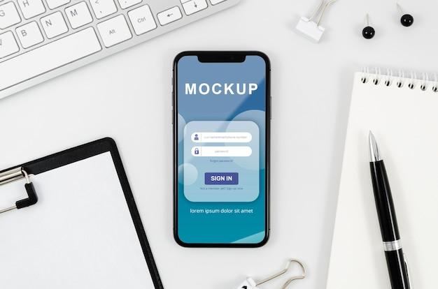 Plat lag smartphonemodel met klembord en pen op bureau Gratis Psd