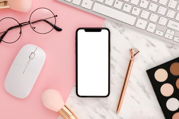 Plat lag smartphonemodel met make-uptoebehoren op bureau Gratis Psd