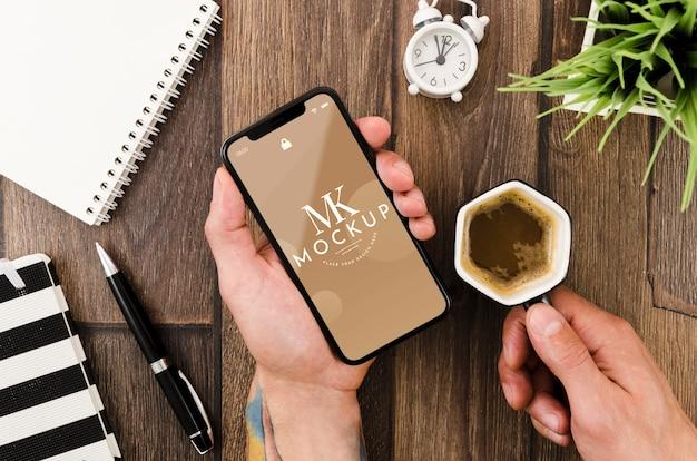 Plat leggen handen met smartphone mock-up en koffie Gratis Psd