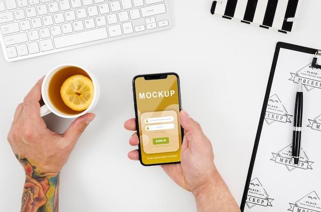 Plat leggen handen met smartphone mock-up en thee Gratis Psd
