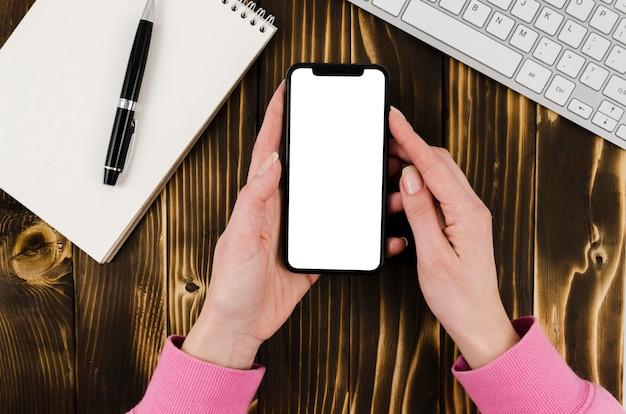 Plat leggen handen met smartphone mock-up met blocnote Gratis Psd
