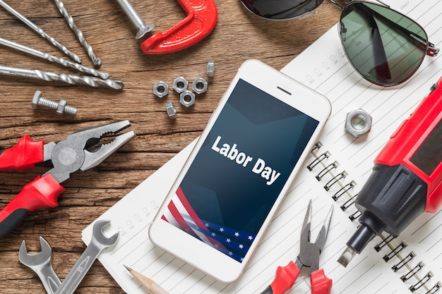 Plat leggen mock-up smart phone met labor day usa holiday en essentiële constructie-instrumenten Premium Psd