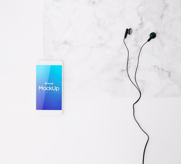Plat leggen smartphone mockup op de werkruimte Gratis Psd