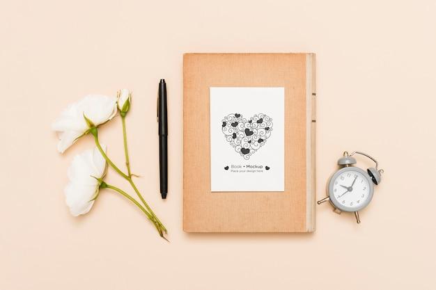 Plat leggen van boek met klok en rozen Gratis Psd