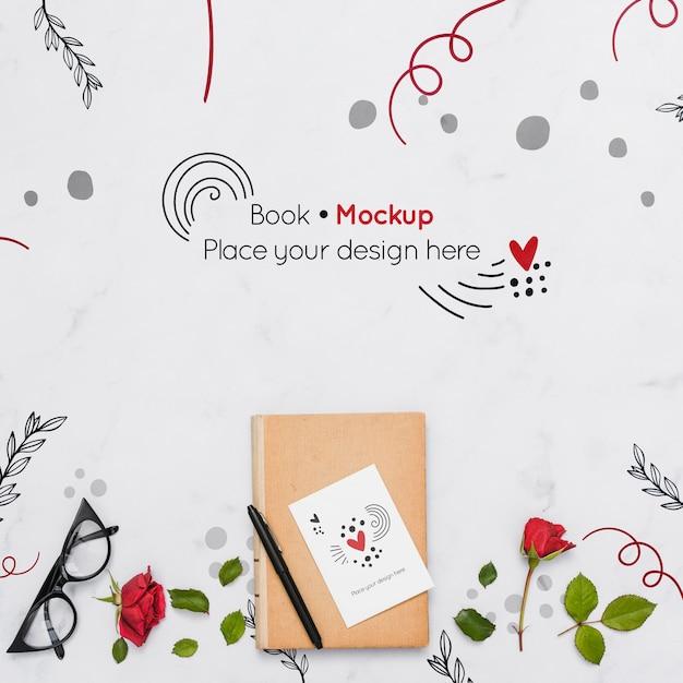 Plat leggen van boek met rozen en glazen Gratis Psd