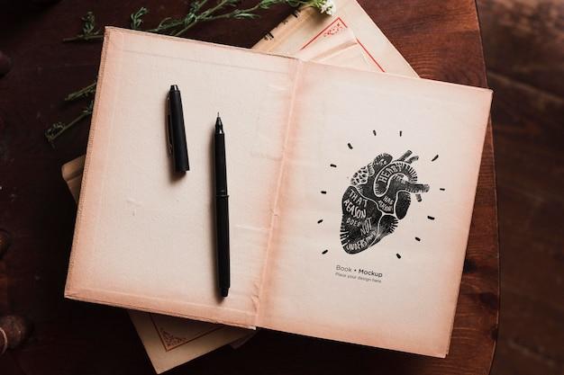Plat leggen van boeken met pen en bloemen Gratis Psd