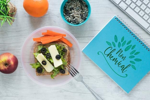 Plat leggen van gezond voedsel met notitieblok mockup Gratis Psd